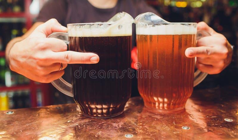 Primo piano della mano del barista al rubinetto della birra che versa una birra chiara del progetto immagine stock libera da diritti