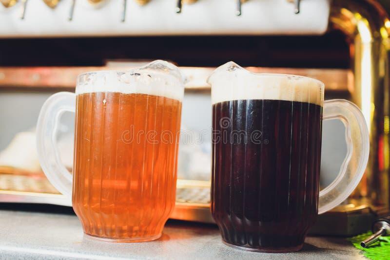 Primo piano della mano del barista al rubinetto della birra che versa una birra chiara del progetto fotografie stock