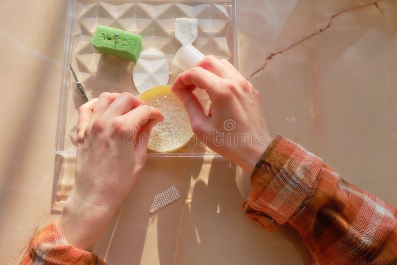Primo piano della mano del needlewoman che fa un ornamento dalle perle fotografie stock libere da diritti
