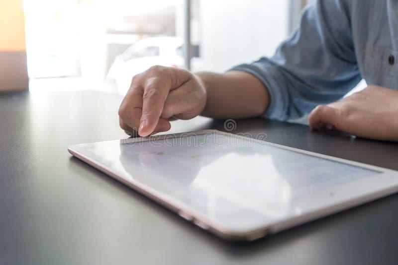 Primo piano della mano del ` s dell'uomo facendo uso della compressa di Digital per controllare immagini stock libere da diritti