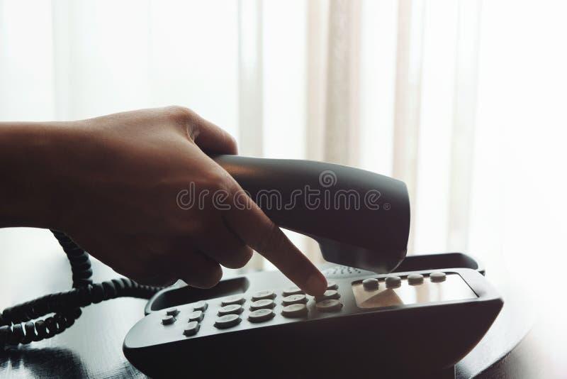 Primo piano della mano del ` s della donna facendo uso di un telefono in nea dell'hotel o della Camera fotografia stock libera da diritti