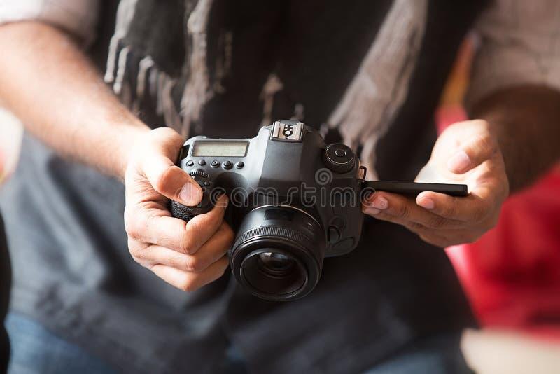 Primo piano della mano dell'uomo che tiene la macchina fotografica del dslr e che prende foto immagini stock