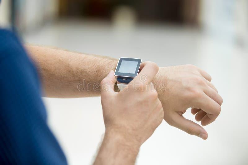 Primo piano della mano dell'uomo con l'orologio astuto