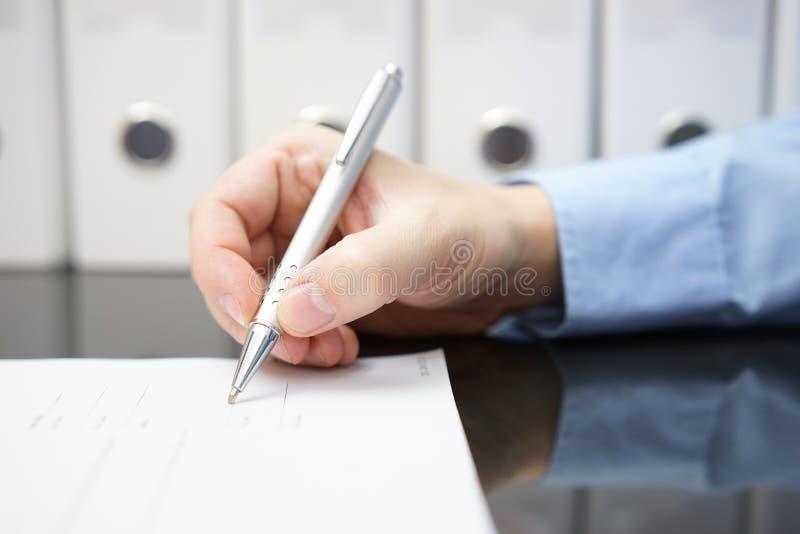 Primo piano della mano dell'uomo d'affari con la penna quando firmano documento Busi fotografia stock