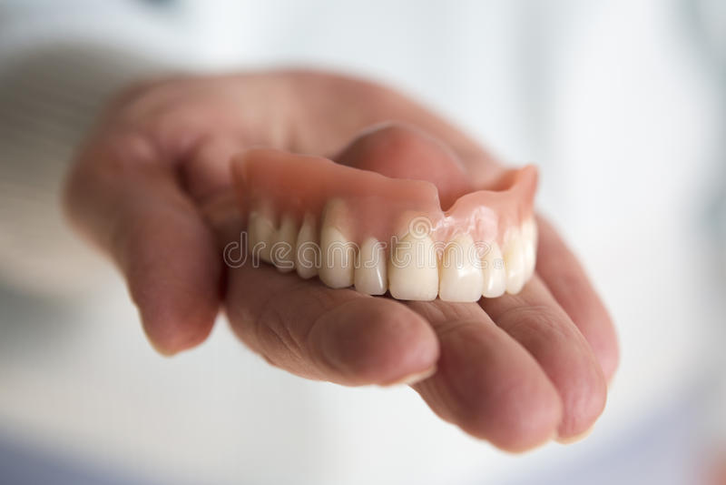Primo piano della mano della donna che tiene una protesi dentaria dei denti fotografie stock
