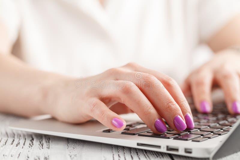 Primo piano della mano della donna di affari con il manicure che scrive sulla tastiera del computer portatile fotografia stock