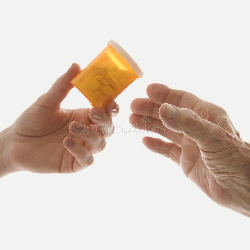 Primo piano della mano della femmina che passa la bottiglia del farmaco alla m. anziana fotografia stock