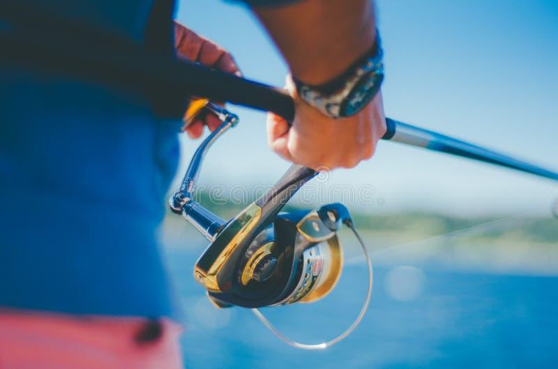 Primo piano della mano di un maschio facendo uso di una canna da pesca fotografia stock