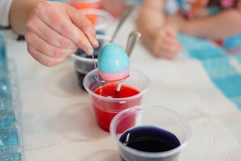 Primo piano della mano della donna che immerge l'uovo di Pasqua a colori tintura immagini stock