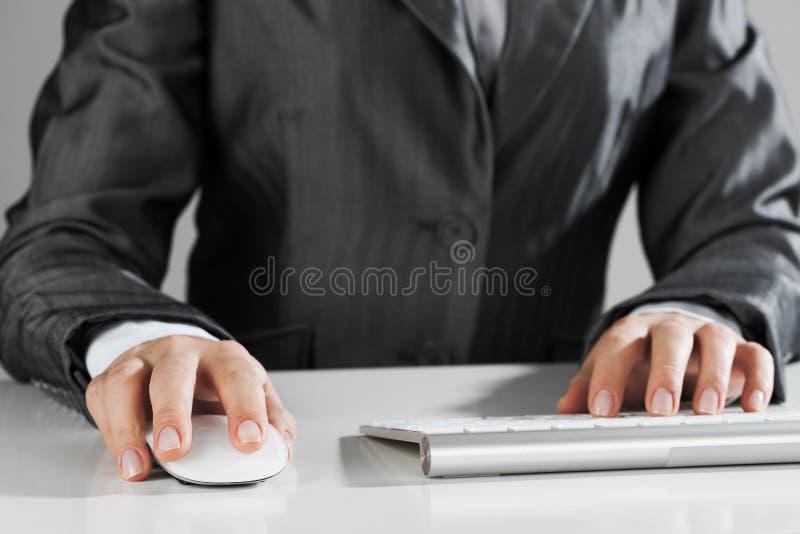 Primo piano della mano della donna di affari che scrive sulla tastiera con il topo sulla tavola di legno fotografia stock libera da diritti