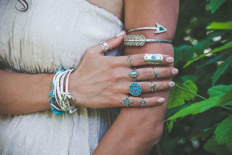 Primo piano della mano e del braccio della giovane donna con il lotto del jewrl di stile di boho immagine stock