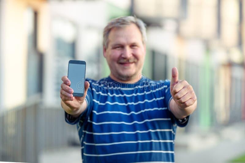 Primo piano della mano felice dell'uomo che mostra schermo in bianco dello smartphone sulla via fotografia stock