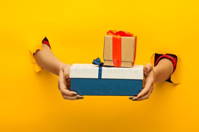 Primo piano della mano femminile che tiene un presente attraverso una carta lacerata, isolato fotografia stock