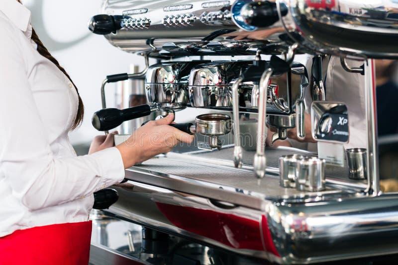 Primo piano della mano femminile sul portafilter di un coffe automatico immagine stock libera da diritti