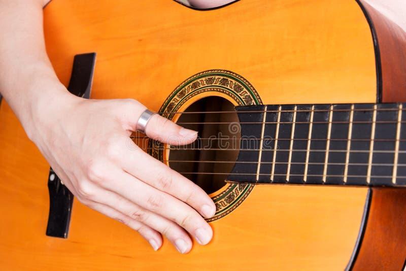 Primo piano della mano della giovane donna che gioca chitarra acustica fotografia stock