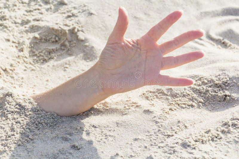 Primo piano della mano Mani sepolte in sabbia su una spiaggia immagini stock libere da diritti