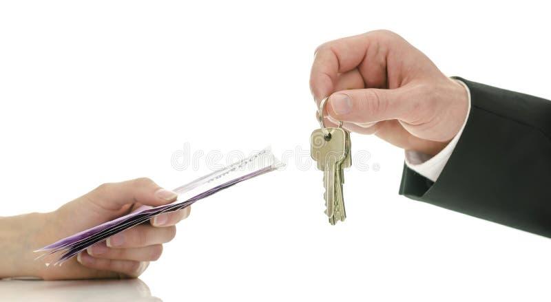 Scambiando soldi per le chiavi della casa immagine stock