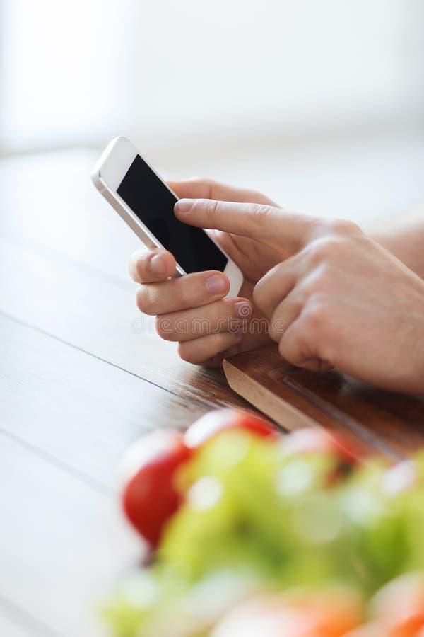 Primo piano della mano maschio che indica dito lo smartphone fotografia stock