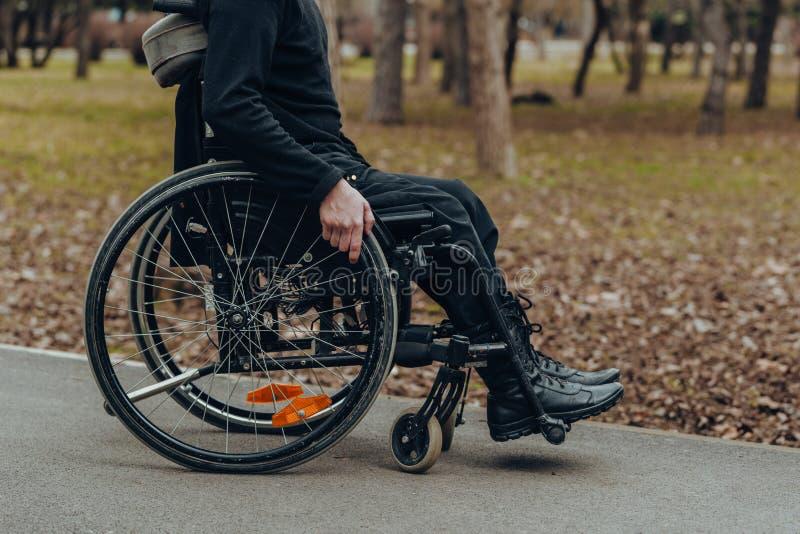 Primo piano della mano maschio sulla ruota della sedia a rotelle durante la passeggiata in parco immagini stock libere da diritti