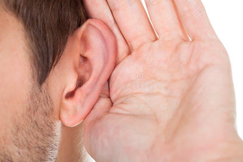 Primo piano della mano vicino all'orecchio immagine stock