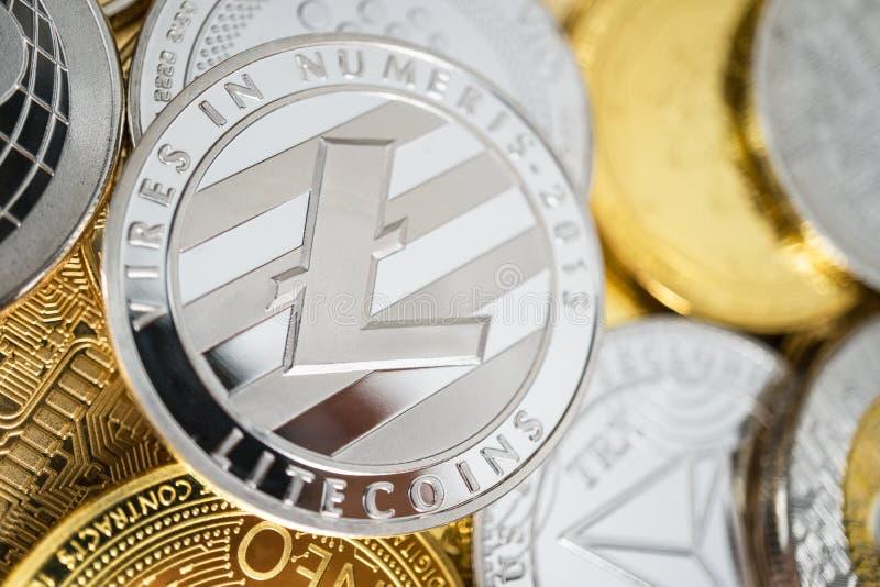 Primo piano della moneta fisica del litecoin sulla pila di molti altri cryptocurrencies fotografia stock libera da diritti