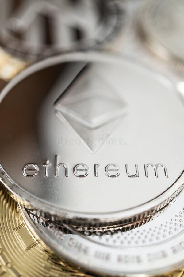 Primo piano della moneta fisica dell'etere sulla pila di molti altri cryptocurrencies fotografia stock