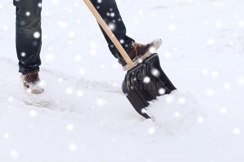 Primo piano della neve di scavatura dell'uomo con la pala fotografie stock libere da diritti