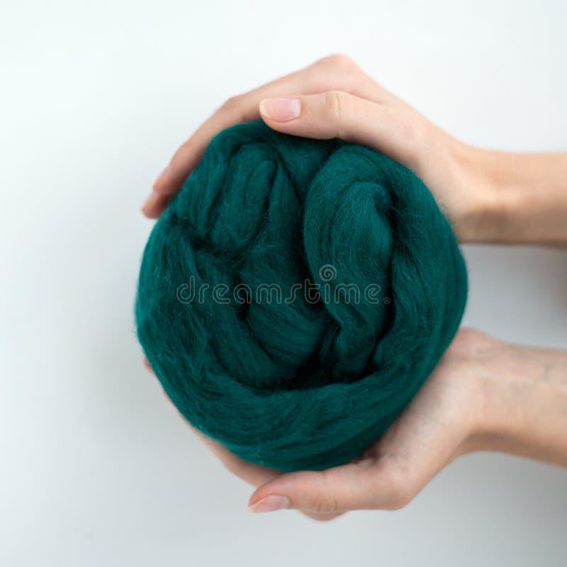 Primo piano della palla grigia della lana merino in mani fotografie stock