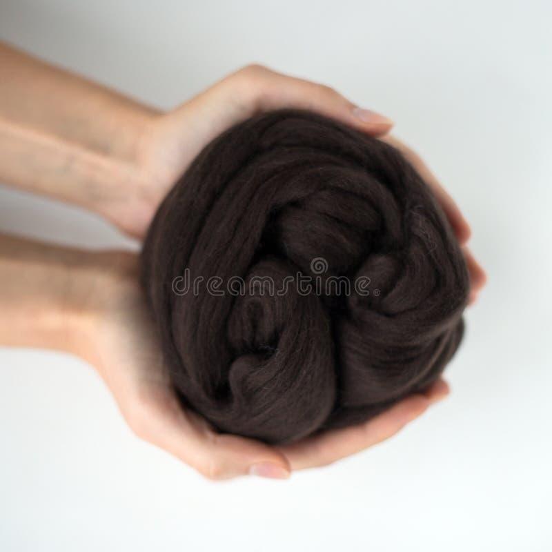 Primo piano della palla nera della lana merino in mani immagini stock