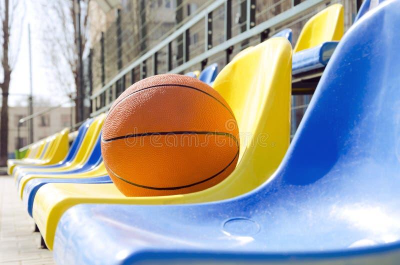 Primo piano della palla sui sedili dello stadio della scuola Concetto della concorrenza di pallacanestro alla corte locale di spo fotografia stock