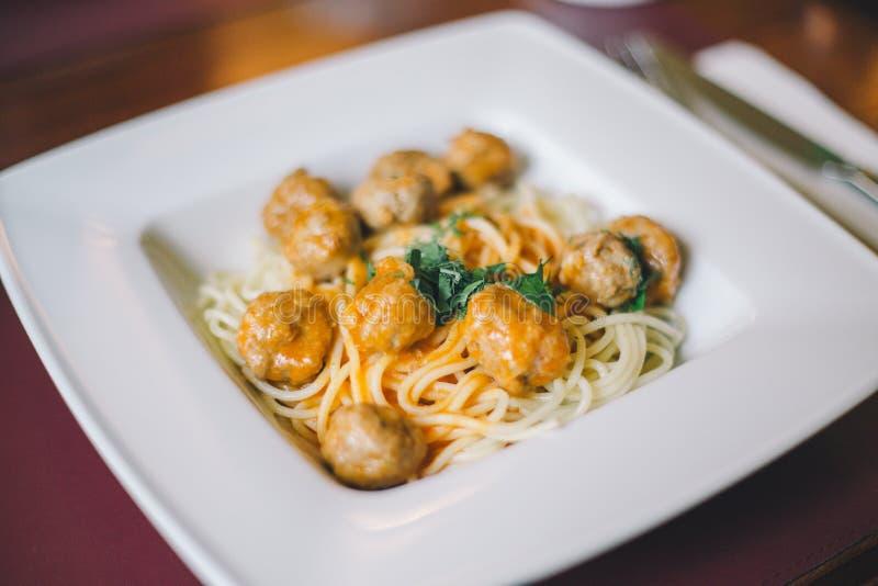 Primo piano della pasta degli spaghetti con le polpette e la salsa al pomodoro in un piatto bianco sulla tavola immagini stock