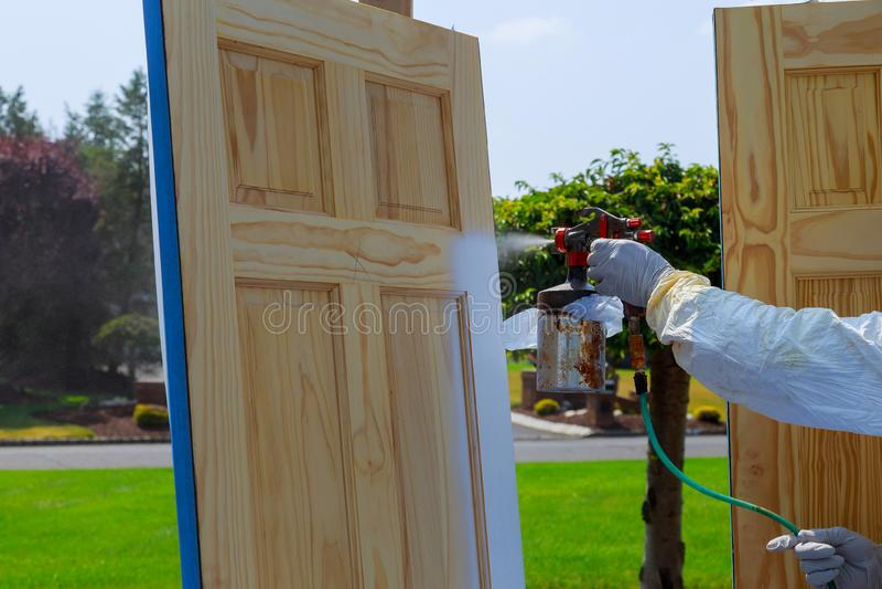 Primo piano della pistola a spruzzo con il Master della pittura della pittura che dipinge le porte di legno fotografia stock libera da diritti