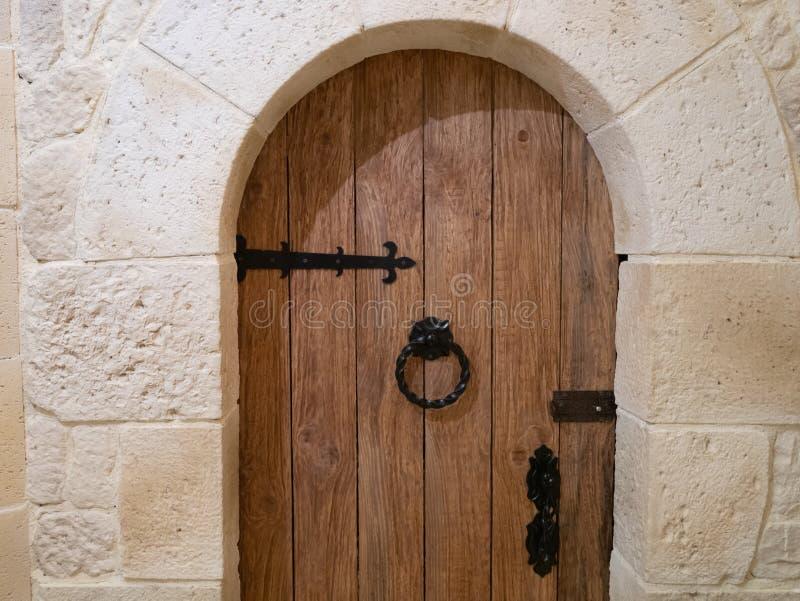 Primo piano della porta di legno d'annata dell'arco con il battitore metallico nello stile mediterraneo fotografie stock