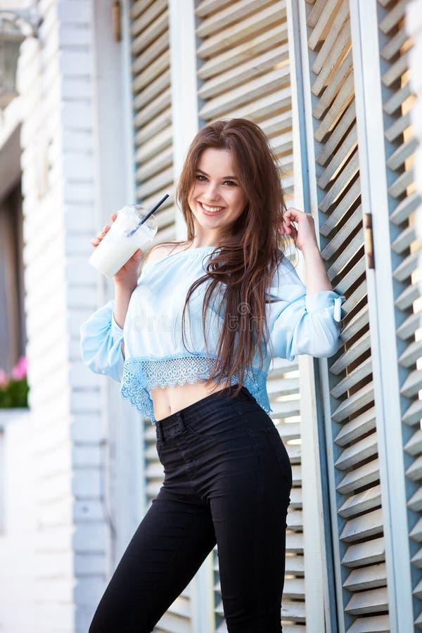 Primo piano della ragazza castana attraente con capelli lunghi che stanno caffè vicino Porta la blusa blu con le spalle aperte immagini stock libere da diritti
