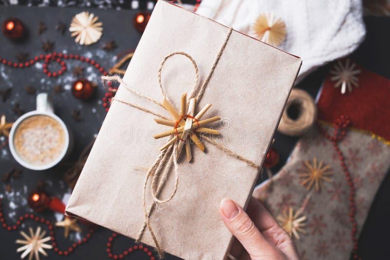 Primo piano della ragazza che tiene una scatola di regalo casalinga di carta kraft sui precedenti della tavola di Natale immagine stock libera da diritti
