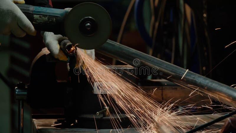 Primo piano della rotazione della smerigliatrice di angolo del disco durante il funzionamento Scintille luminose da per il taglio fotografia stock libera da diritti