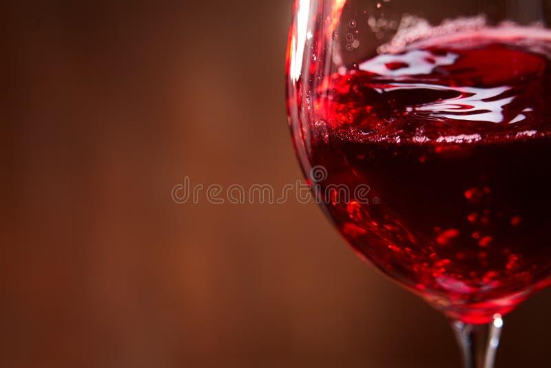 Primo piano della spruzzatura astratta del vino rosso nel bicchiere di vino fragile sui precedenti di legno marroni immagini stock libere da diritti