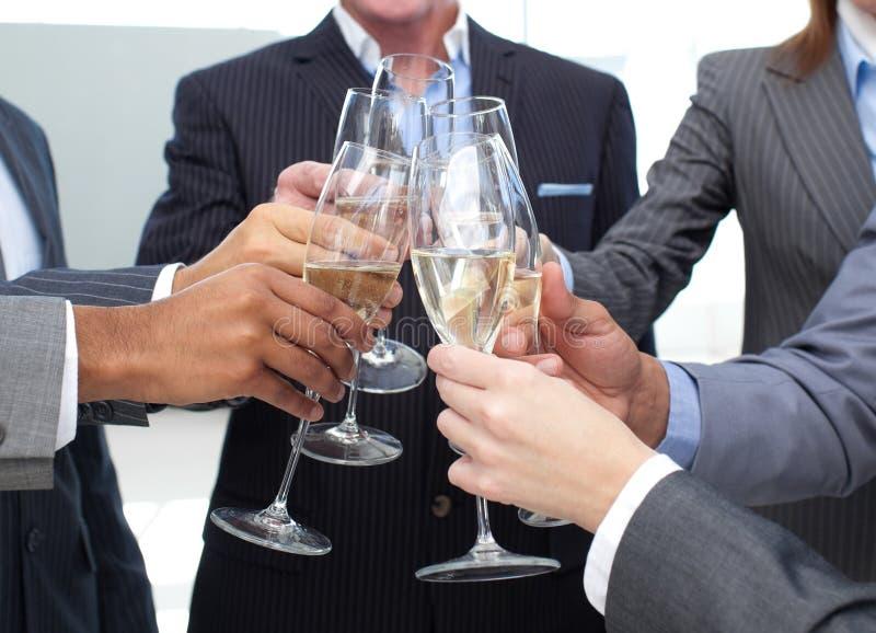 Primo piano della squadra di affari che tosta con Champagne fotografia stock libera da diritti