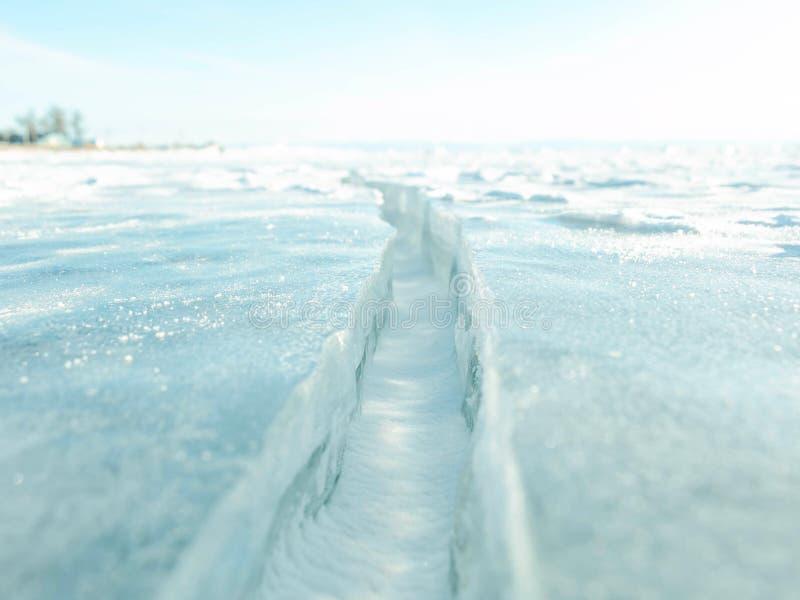 Primo piano della superficie della crepa del ghiaccio; ed orizzonte e cielo blu dietro fotografia stock