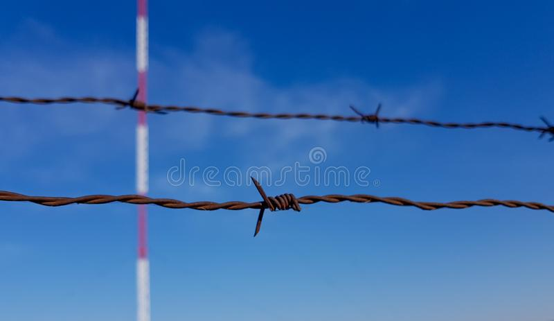 Primo piano della torre di comunicazioni del filo spinato e del fondo proteggenti del cielo blu fotografie stock