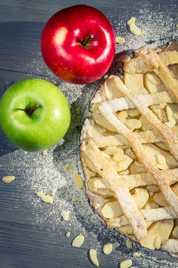 Primo piano della torta di mele con le mandorle, lo zucchero a velo e le mele fotografia stock libera da diritti