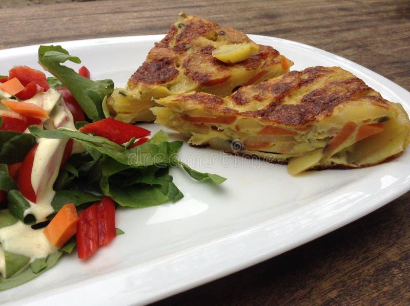 Primo piano della tortiglia spagnola con insalata fotografia stock