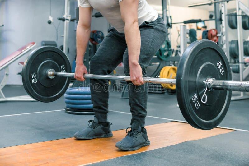 Primo piano delle armi e gambe dell'uomo che si esercitano con il bilanciere alla palestra di sport Atleta, culturismo, addestram fotografia stock libera da diritti