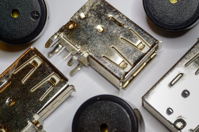 Primo piano delle componenti sparse di elettronica dell'incavo e del cicalino di USB su fondo bianco nel fuoco parziale e nel mod immagini stock