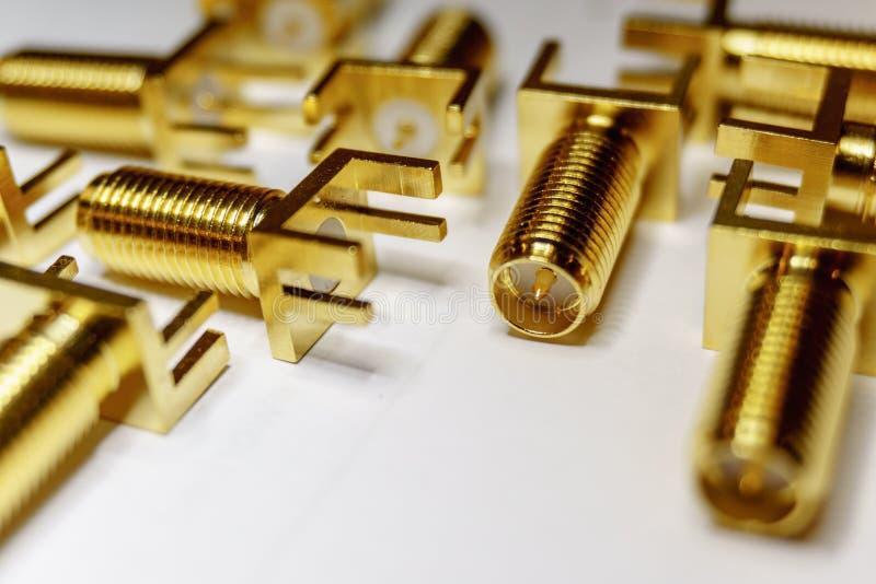 Primo piano delle componenti sparse di elettronica placcate oro dei connettori maschii di SMA nel fuoco parziale su fondo bianco  fotografie stock