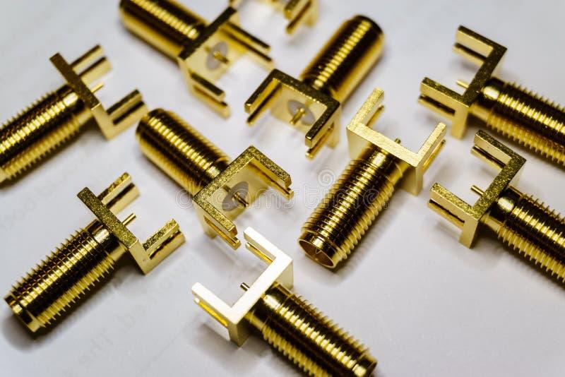 Primo piano delle componenti sparse di elettronica placcate oro dei connettori maschii di SMA su fondo bianco nel modello casuale fotografia stock