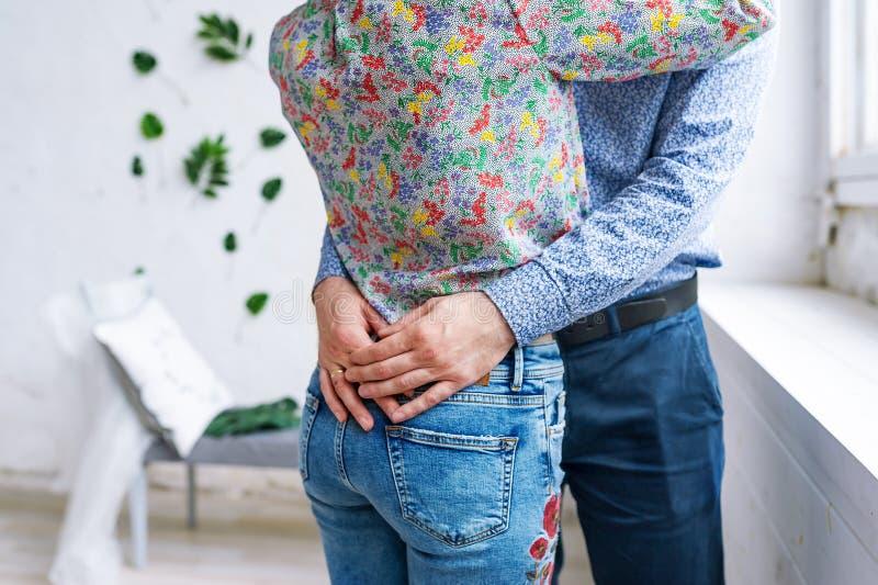 Primo piano delle coppie alla stanza bianca Uomo in un'usura convenzionale che abbraccia dalla vita una donna, jeans sexy d'uso fotografia stock