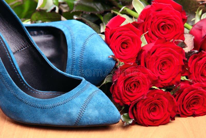 Primo piano delle coppie i pattini femminili blu e le rose rosse fotografia stock