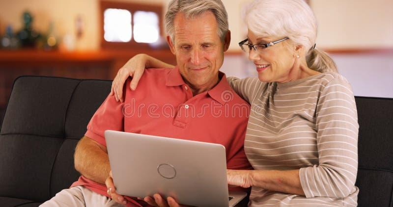 Primo piano delle coppie senior facendo uso del computer portatile a casa immagini stock libere da diritti