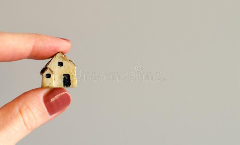 Primo piano delle dita del ` s della donna che tengono casa di plastica minuscola fotografia stock